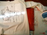 """I used a handy art board on its way to Japan to wrap up my shirt.  You can also use a box, piece of cardboard, whatever.  I tape down the edges of the stencil to the fabric at this point, to cut down on """"blowback."""""""
