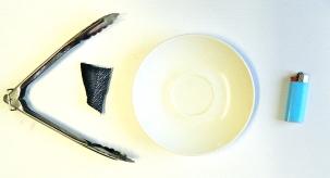 Tongs, scrap of fabric, saucer, lighter.